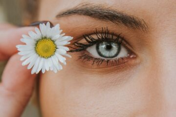 Women holding a small daisy near her eye lashes. Women is wearing mascara