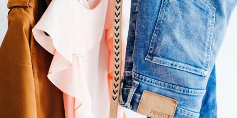 A coat, top, belt and denim jeans hanging on a clothes rack.