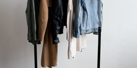 capsule wardrobe with few items of clothing hanging on the clothing rack