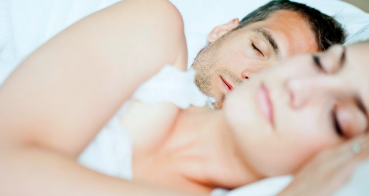 Couple peacefully sleeping in bed with white bedding