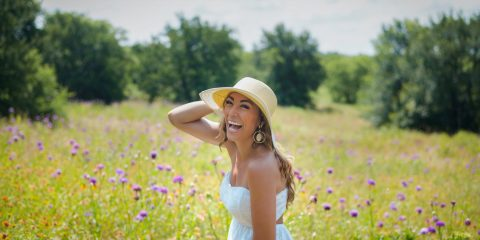 A women wearing a straw hat and a white summer dress in a field laughing