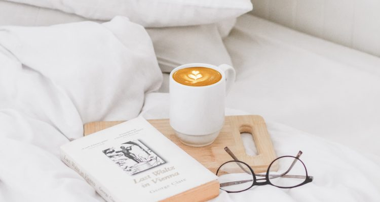 White linen bedding with a book. reading glasses and coffee cup on the bed