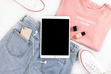 Ipad on top of a pair of denim jeans, pink t-shirt and a pair of converses next to it