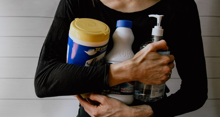 Women with a black top sitting on the floor, legs crossed holding cleaning products in her hands