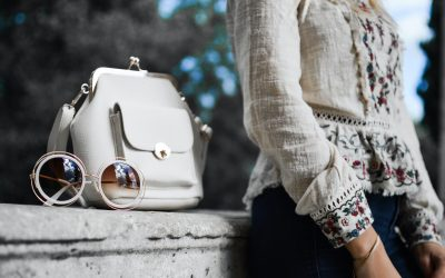 Women wearing a lovely top with elegant handbag and retro sunglasses next to here