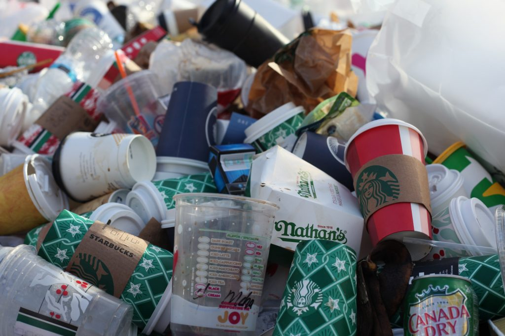 Lots of single use coffee plastic cups in a rubbish pile