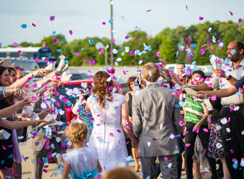 couple married and everyone throwing wedding confetti on them on a beautiful sunny day