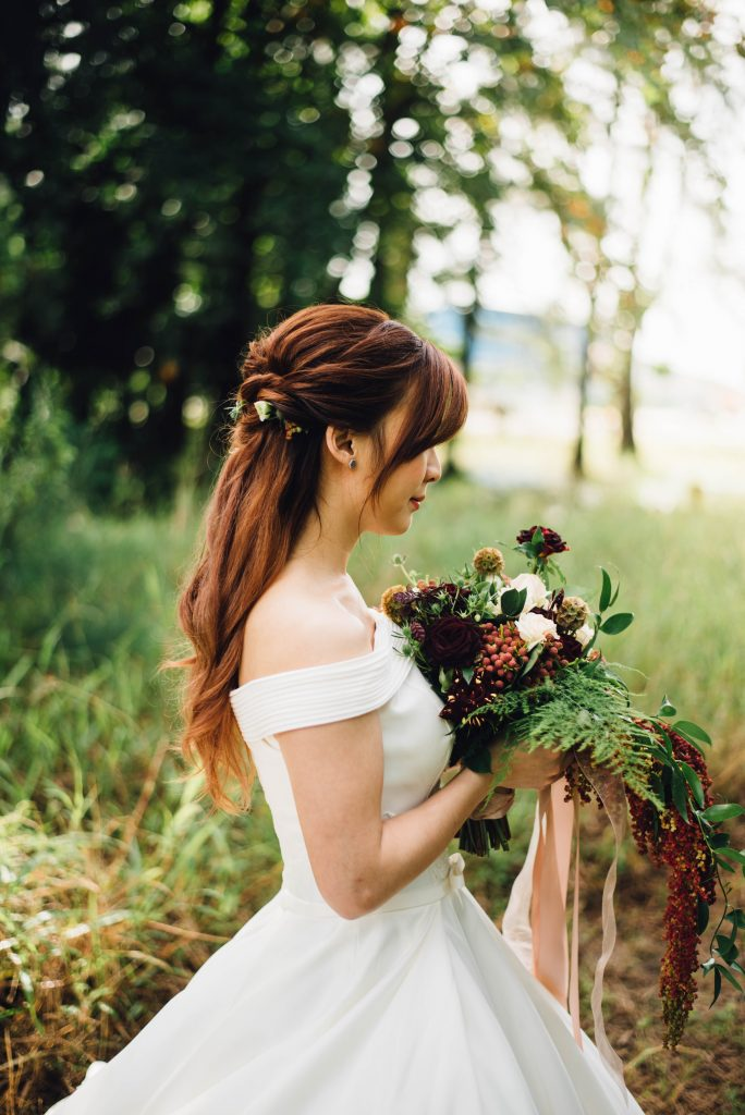 woman walking down the woodland with fresh wedding bouquet