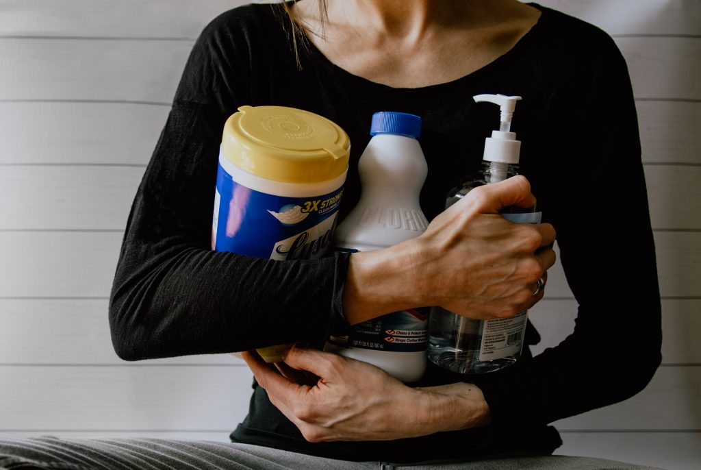 Woman holding cleaning products in her hands
