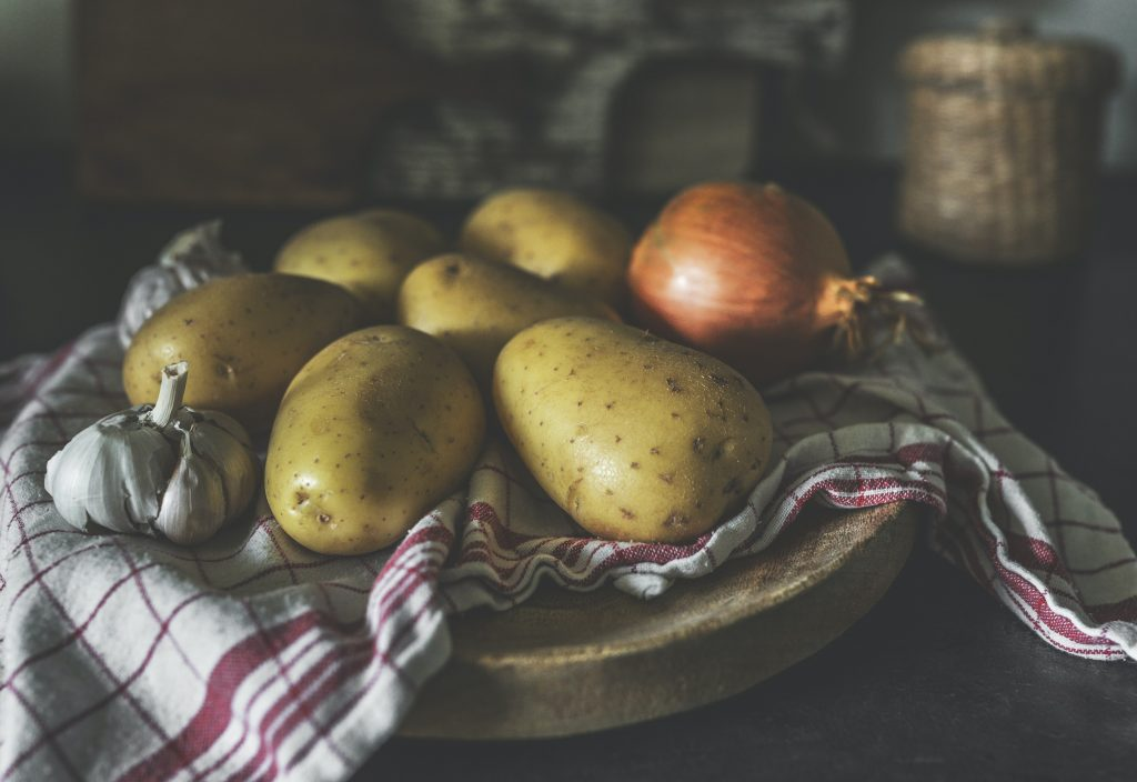 potatoes, garlic, onions on a table with a napkin