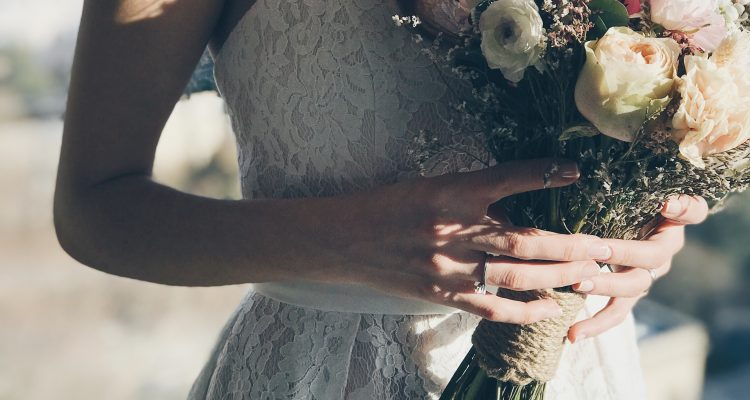 Bride holding beautiful natural flowers in her hand with a lace wedding dress