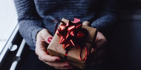 Woman holding a gift in her hands that is wrapped in brown paper and red ribbon
