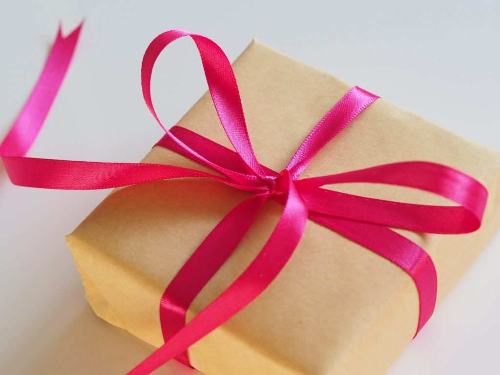 a present wrapped in brown paper with pink ribbon