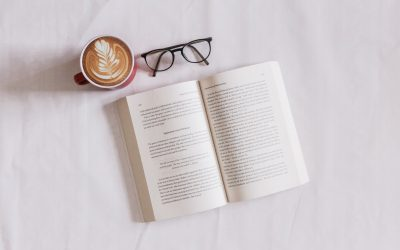 a pair of glasses, book and a cup of coffee on a bed