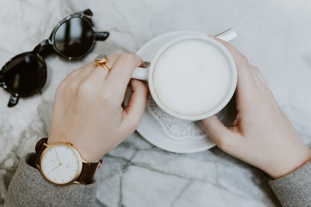 a woman wearing a watch on her wrist and drinking coffee