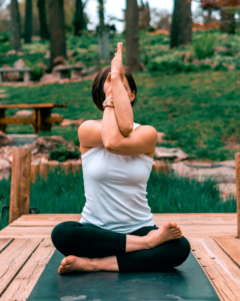 woman folding her hands together in yoga position