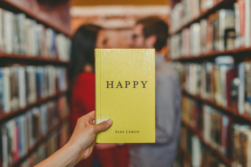 a woman holding a yellow book with the title Happy