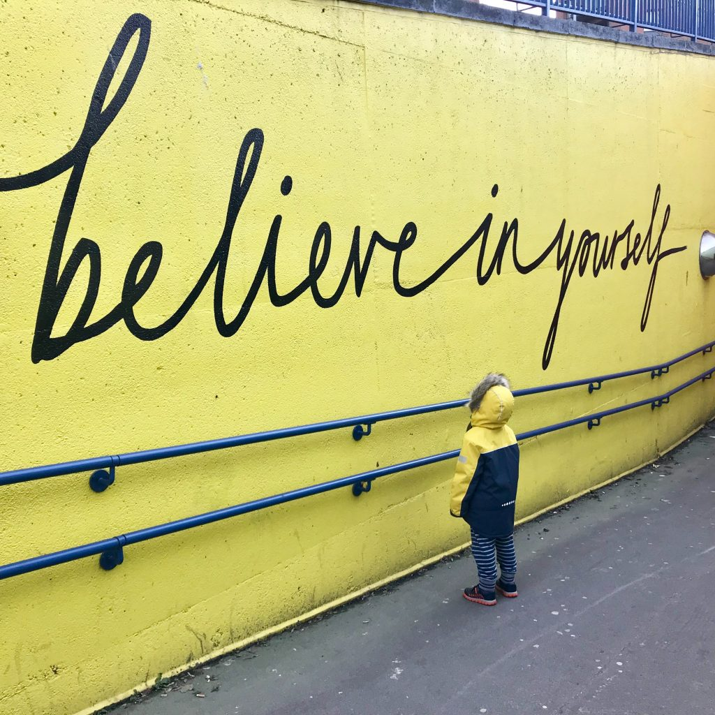 yellow wall with a child looking at it, wall has believe in yourself written on it