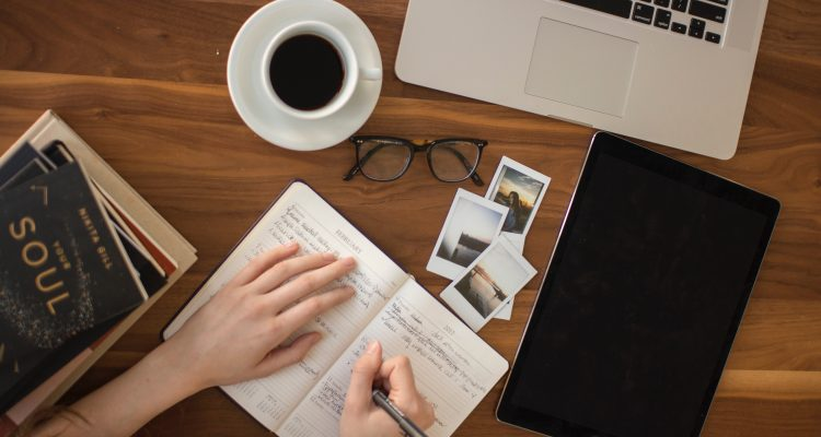woman writing in a journal with a cup of coffee next to her on the table and a pair of glasses