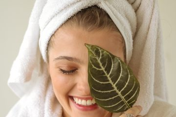 woman holding a leaf to her face wearing a bath robe