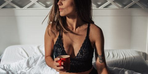 woman sitting on bed drinking coffee with black bralette and black pants