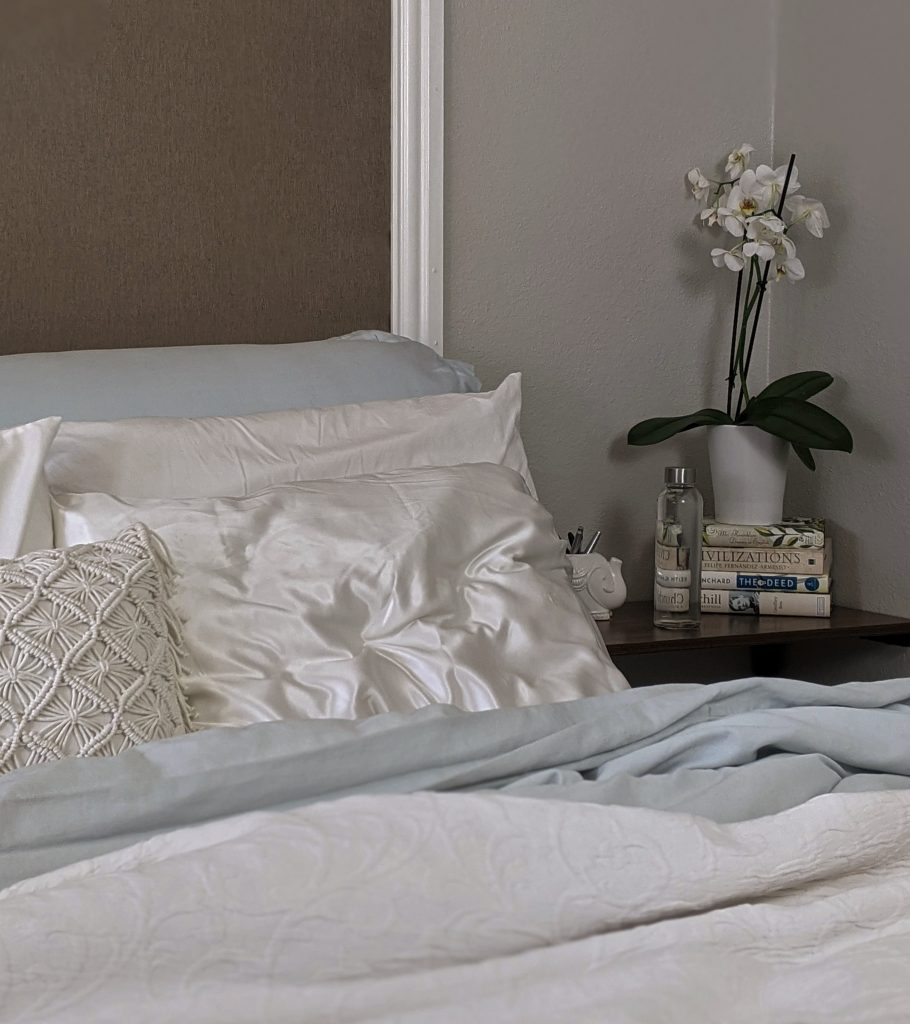 white pillows and white bedding with flowers on a bedside table