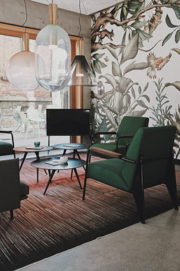 green leaf wallpaper in a living room with green sofas and green coffee table
