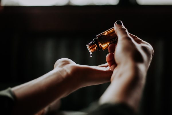 woman putting oil on her hands from a bottle