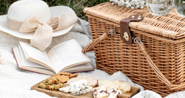 wicker picnic basket and cheese board on the grass