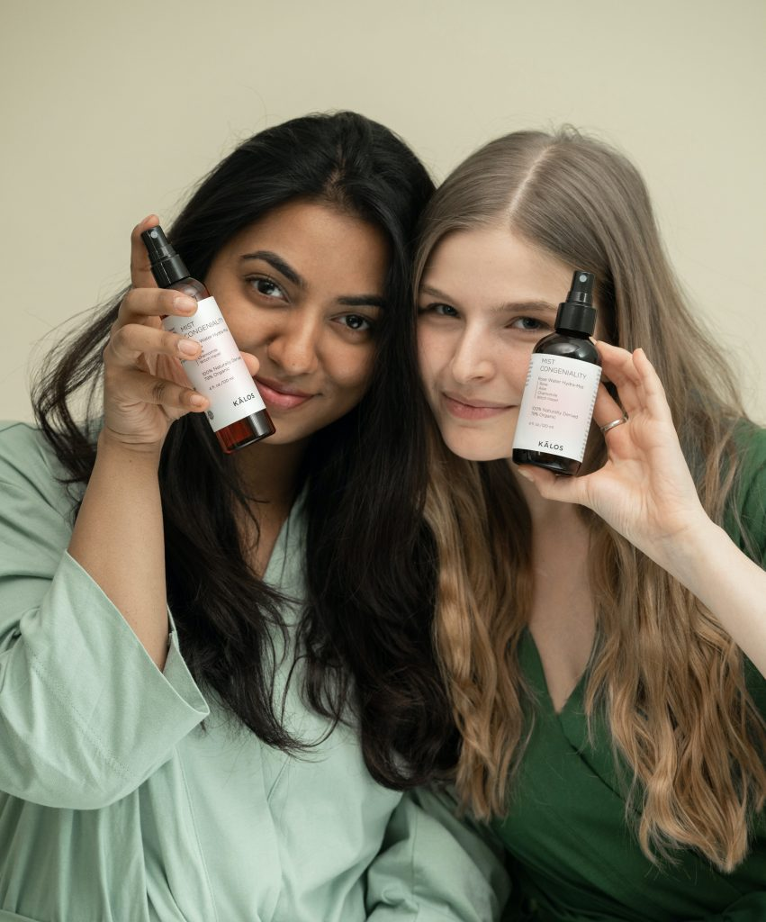 two friends holding up skin care products smiling