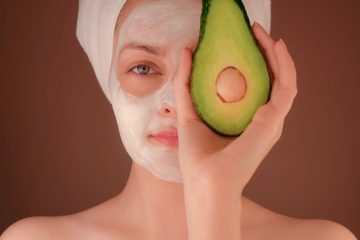 woman wearing a face mask and holding an avocado