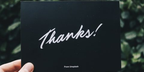 woman holding a card saying thanks