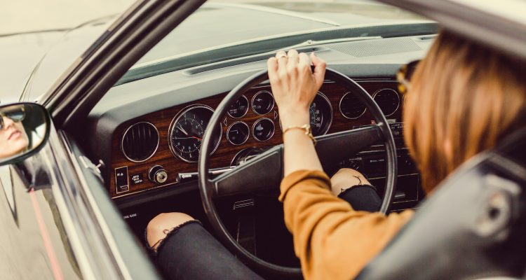 woman driving a car wearing yellow sweater and black ripped jeans