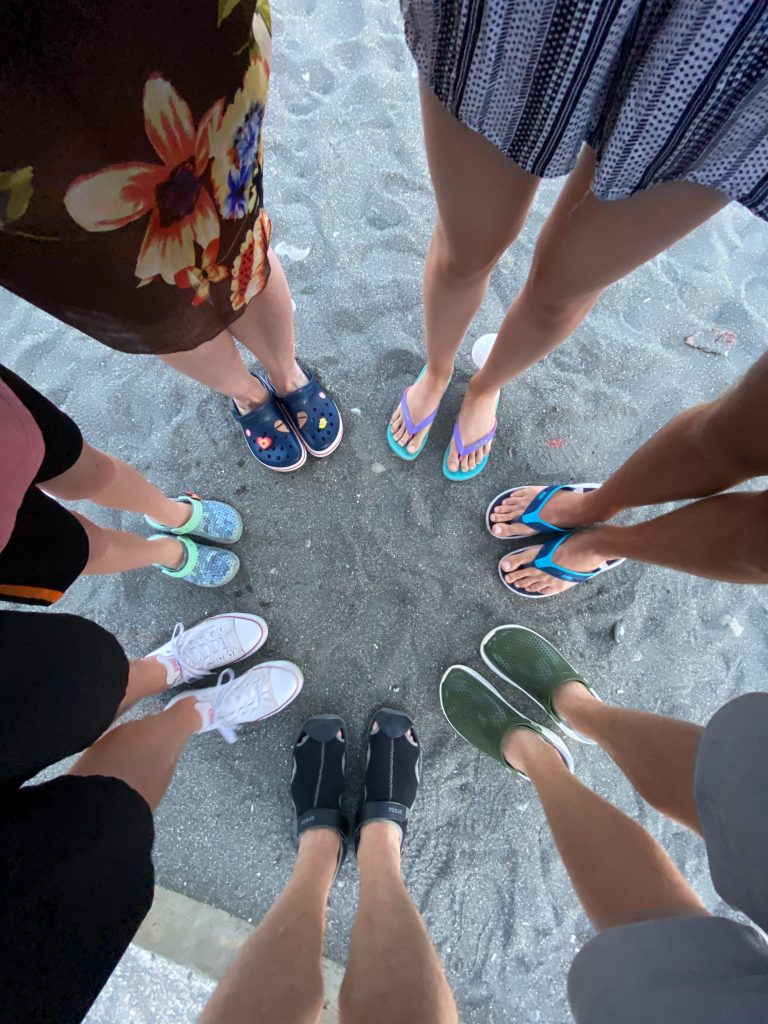 family wearing different types of footwear standing on a beach in a circle