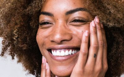beautiful women smiling happy touching her face with her fingers feeling her smooth skin