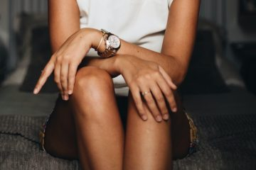 woman sitting with her legs crossed wearing a white top and short skirt