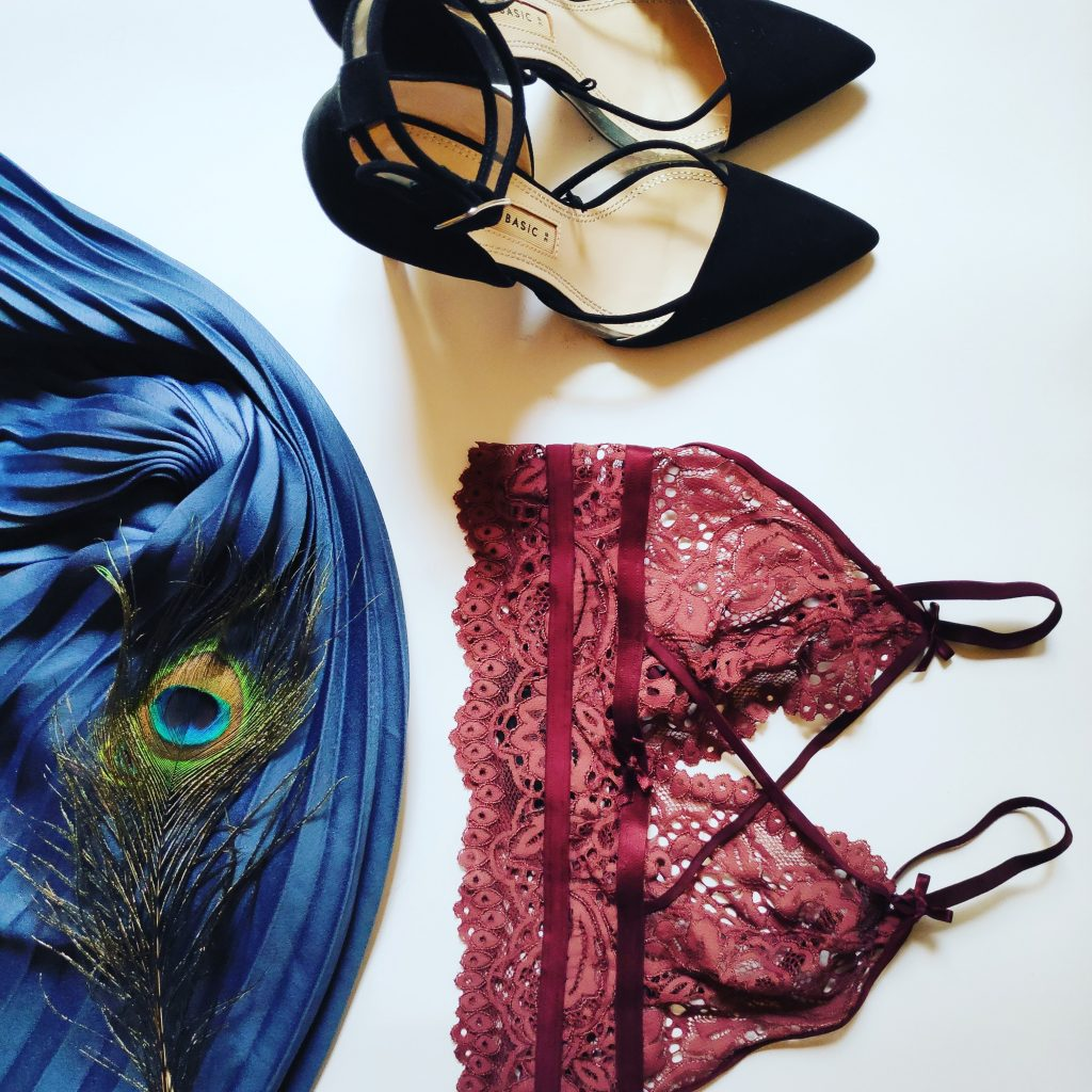 purple bralette and black high heel shoes with a peacock feather on a white table
