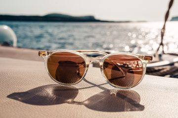 sunglasses on a table with the sun shining on them
