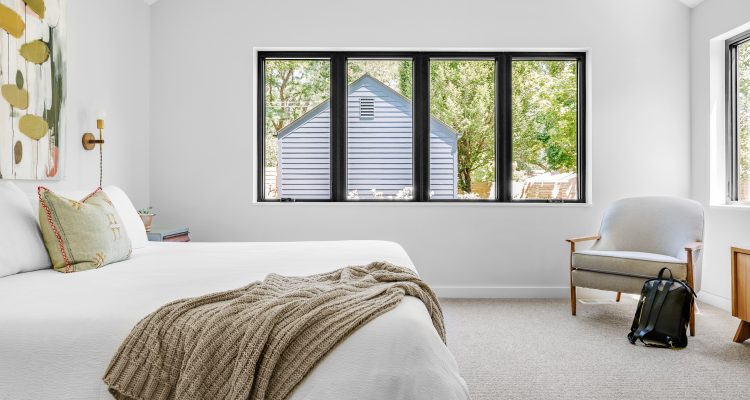 bedroom with double bed and white covers with a big window