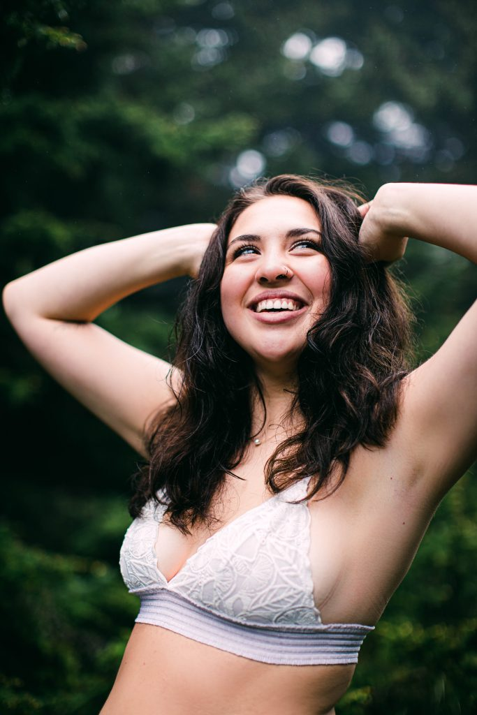 woman wearing a white bralette laughing with long brown hair